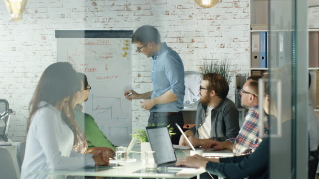 Man Makes Whiteboard Presentation to His Creative Office Staff. Coworkers Sit at the Big Glass Table with Open Laptops, Taking Notes. Office is Stylish and Bright.
