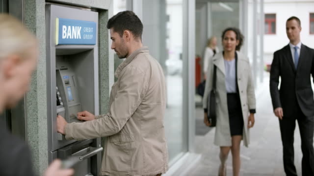 man making a withdrawal from the atm machine on a busy street - banks and atms stock videos & royalty-free footage