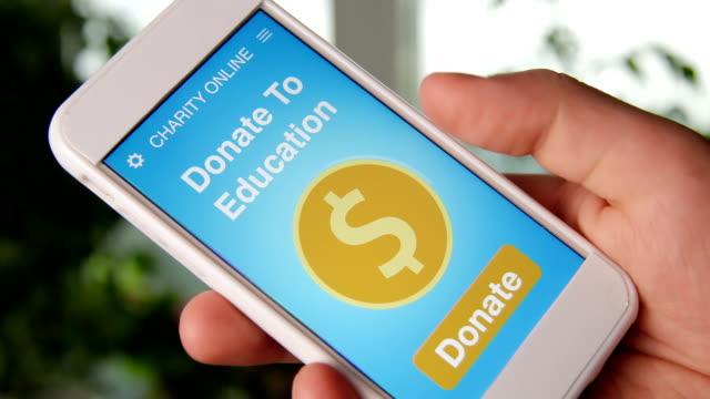 vídeos de stock e filmes b-roll de man making an online donation to education using charity applicaiton on smartphone - benefits