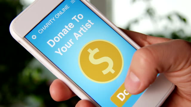 Man making an online donation to his favorive artist using charity applicaiton on smartphone video