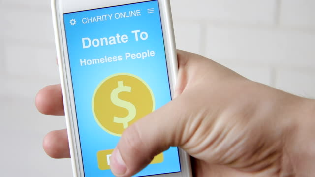 Man making an online donation to homeless people using charity applicaiton on smartphone Stock footage Man making an online donation to homeless people using charity applicaiton on smartphone homeless shelter stock videos & royalty-free footage