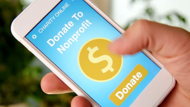 man gör en online donation till ideell organisation med välgörenhet ansökan på smartphone - välgörenhet bildbanksvideor och videomaterial från bakom kulisserna