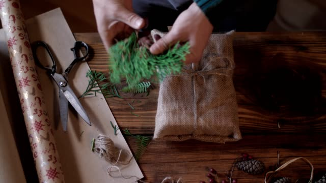 Man Making Christmas Gifts. Stock video of unrecognizable man wrapping Christmas gifts, ecological materials with plastic free. wrapped stock videos & royalty-free footage