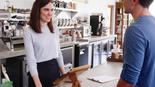 vidéos et rushes de homme faisant paiement smartphone sans contact à un café-restaurant - relation client