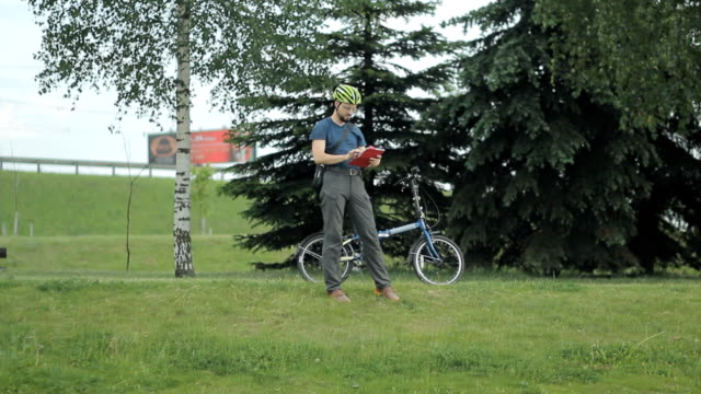 man making photo with tablet at park - blazer video stock e b–roll