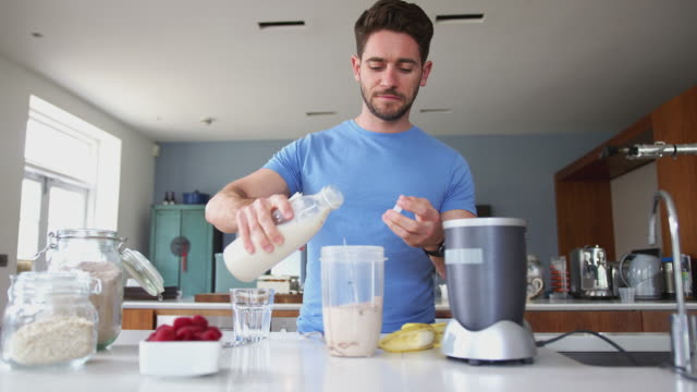 Man Making Protein Shake After Exercise At Home Man wearing fitness clothing adding almond milk to ingredients in blender for healthy protein shake - shot in slow motion protein stock videos & royalty-free footage