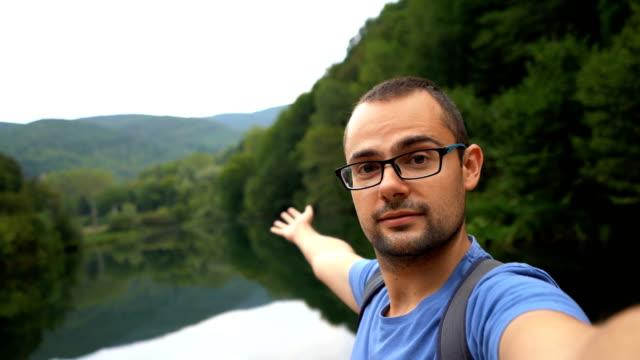 vídeos de stock e filmes b-roll de man making video call by the river - man admires forest