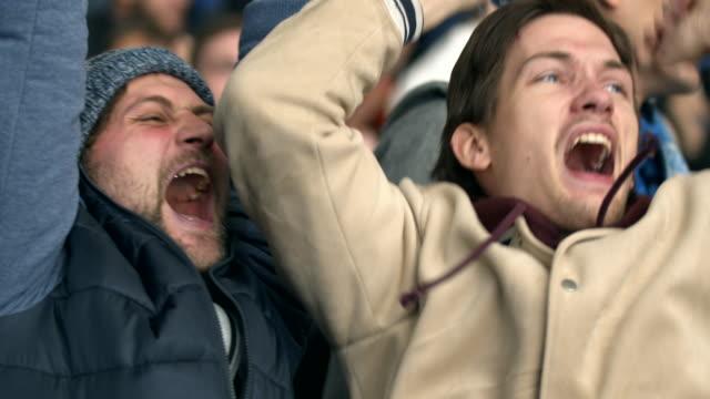 vídeos de stock e filmes b-roll de man match hockey fun goal winning close up fan emotion screaming crowd guy 4k. - soccer supporter portrait