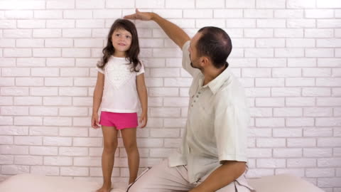 A man measures the growth of a child. A man measures the growth of a child. Father measures the growth of his daughter. high up stock videos & royalty-free footage