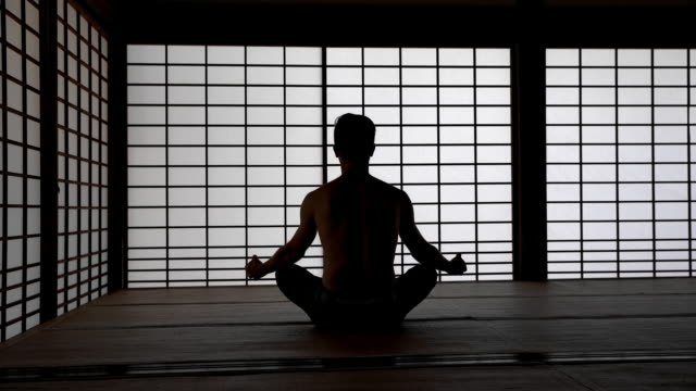 DS Man meditating in tatami house Dolly shot of a silhouette of a man meditating in traditional Japanese tatami house. Also available in 4K resolution cross legged stock videos & royalty-free footage