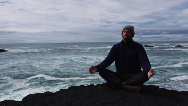man meditating on a rocky shore - gente serena video stock e b–roll