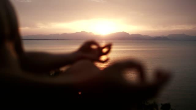 man meditation. rocky coastline at sunset - mindfulness stock videos & royalty-free footage