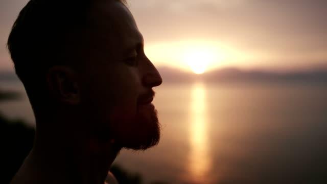 Man meditation. Rocky coastline at sunset