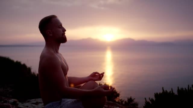 Man meditation. Rocky coastline at sunset Man meditating in lotus pose. Looking at distant sea lotus position stock videos & royalty-free footage