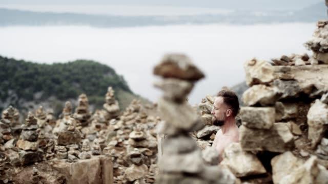 남자 명상입니다. 바위 해안선 - 한 명의 중년 남자만 스톡 비디오 및 b-롤 화면