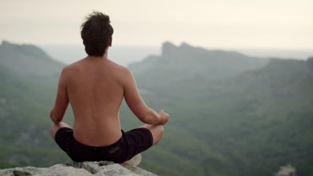mann-meditation. felsige küste - nackter oberkörper stock-videos und b-roll-filmmaterial