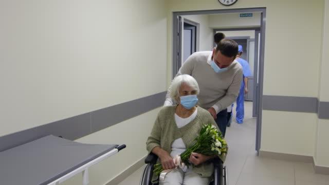 man möte senior mor på rullstol på sjukhus efter återhämtning - hospital studio bildbanksvideor och videomaterial från bakom kulisserna