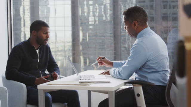 Man Meeting With Male Financial Advisor In Office And Discussing Document