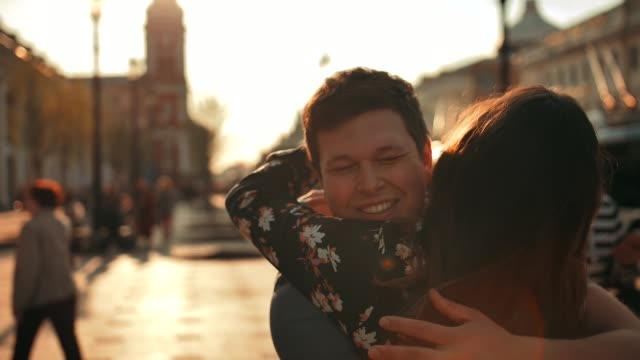 a man meets a woman walking down the street and gives her a hug, close up - abbracciare una persona video stock e b–roll