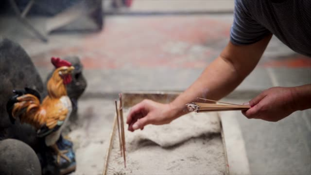 man methodically puts burning incense on asian rooster shrine video