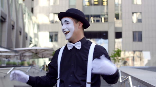 帽子の男 mime 身振りカメラの前で彼の手を入れて話します - グリースペイント点の映像素材/bロール