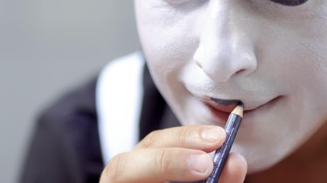 man mime paint his lips with black pencil - гримировальные краски стоковые видео и кадры b-roll
