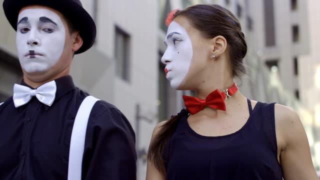 man mime pushing his girlfriend away from the shot - гримировальные краски стоковые видео и кадры b-roll