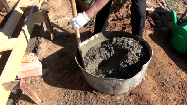 Man mixing concrete cement with water