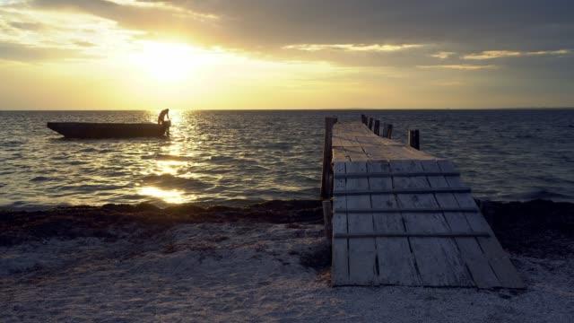 adam gün batımında bir tekne demirler - dalgakıran stok videoları ve detay görüntü çekimi