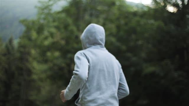 男朝のジョギング山林でスローモーションに顔はないです。男性ジョガーの側背面はグレーのフード付きセーターとトレーニング パンツの丘を実行します。ウェルネス トレーニング屋外の新鮮な空気のライフ スタイル - 灰色点の映像素材/bロール