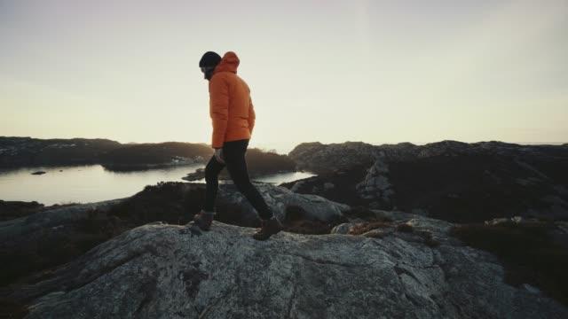 vídeos y material grabado en eventos de stock de montaña del hombre del senderismo por un fiordo en noruega - bergen
