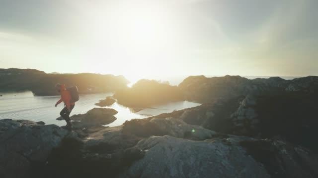 vídeos de stock e filmes b-roll de man mountain hiking by a fjord in norway - países nórdicos