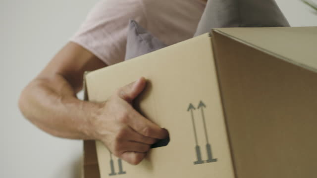Man moving into a new house A mature hispanic man is packing and unpacking as he is moving into a new house. He is moving boxes around. unpacking stock videos & royalty-free footage