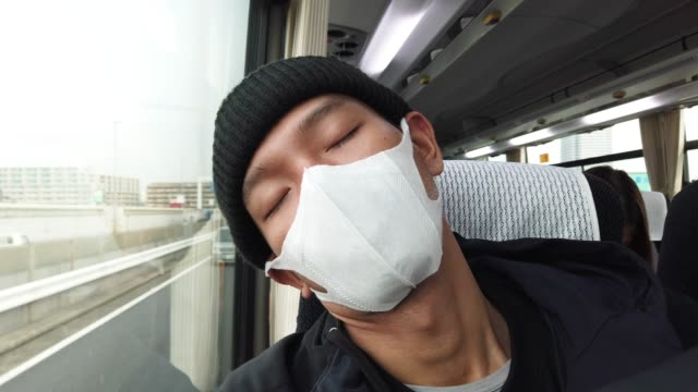 man nap on bus wearing a mask and beanie - smog video stock e b–roll