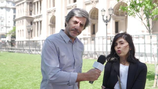 vidéos et rushes de journaliste de nouvelles d'homme interviewant la femme sur la rue - interview