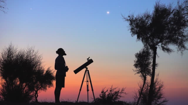 a man observing the night sky - astronomia video stock e b–roll
