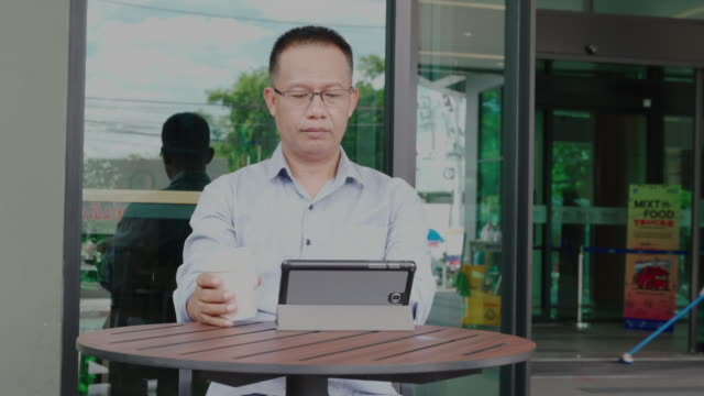 man of asian descent, aged 40-50, wear casual clothes sitting and drinking coffee and using a tablet at a coffee shop ,happiness means everything as inspiration concepts, - sud est asiatico video stock e b–roll