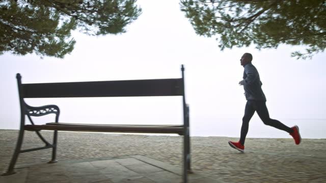 SLO MO Man on a morning run on a footpath along the sea
