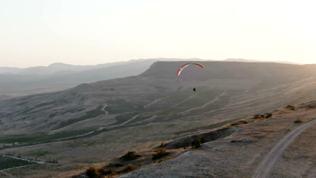 AERIAL: A man on a paraglider flies during sunset over a valley. The last rays of the sun illuminate his wing. A sense of freedom fills the chest.