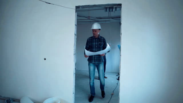 Man on a site with blueprint A taskmaster walking on a construction site with the plan then he stop and looking on camera and smile craftsman architecture stock videos & royalty-free footage