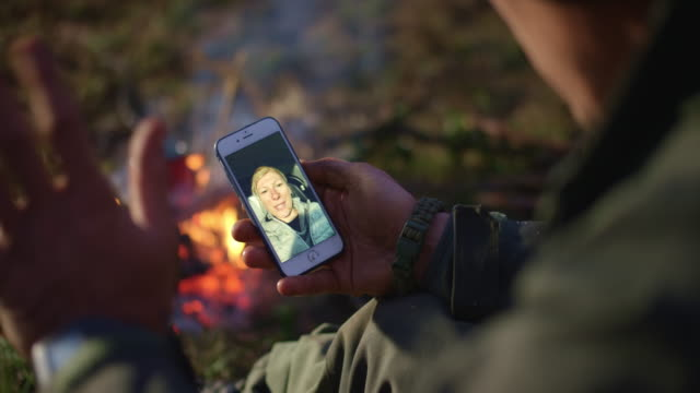 man on a videocall with his wife while sitting by the campfire - дикая местность стоковые видео и кадры b-roll