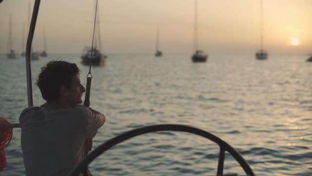 man on a yacht enjoys sunset on cala saona bay. luxury yacht near the formentera island. slow motion - ibiza filmów i materiałów b-roll