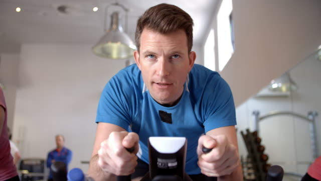 Man on an exercise bike in a exercising class at a gym, close up Man on an exercise bike in a exercising class at a gym, close up exercise bike stock videos & royalty-free footage
