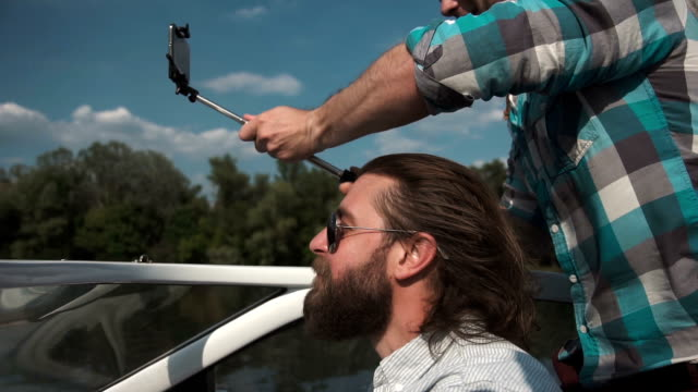 Man on boat with friends taking selfie video