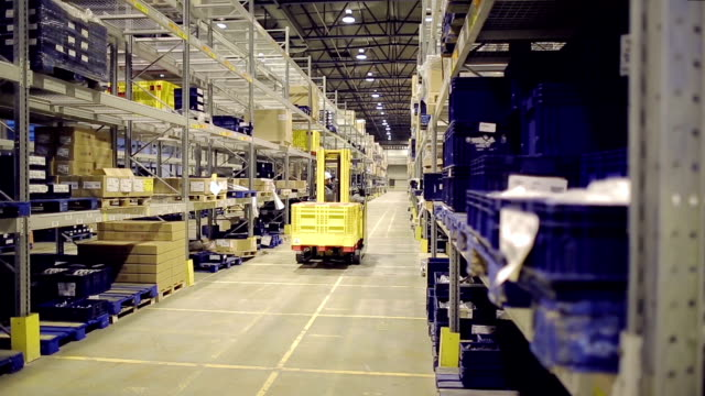 vídeos de stock e filmes b-roll de man on forklift riding and loading cargo on rack - engradado