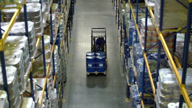 man on forklift transporting barrels in warehouse - cask video stock e b–roll