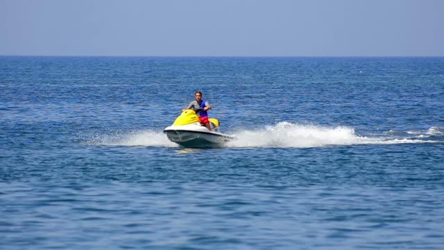 man on jet ski drive to lighthouse island. A man cruises the ocean on a jet ski with sail boat on horizon