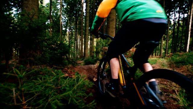Man on mountain bike jumps in slow motion in woods video