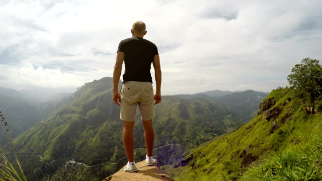 Man on mountain spreading arms Man standing on edge of abyss before green hills and spreading his arms sri lanka stock videos & royalty-free footage