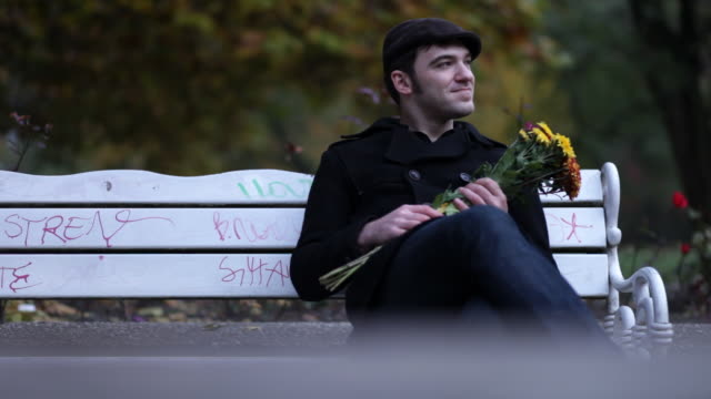 vídeos de stock, filmes e b-roll de homem no banco de parque, esperando data, olhando relógio - solteiros jovens